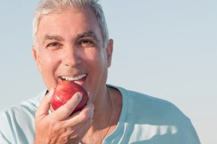 older-man-biting-into-an-apple-outdoors